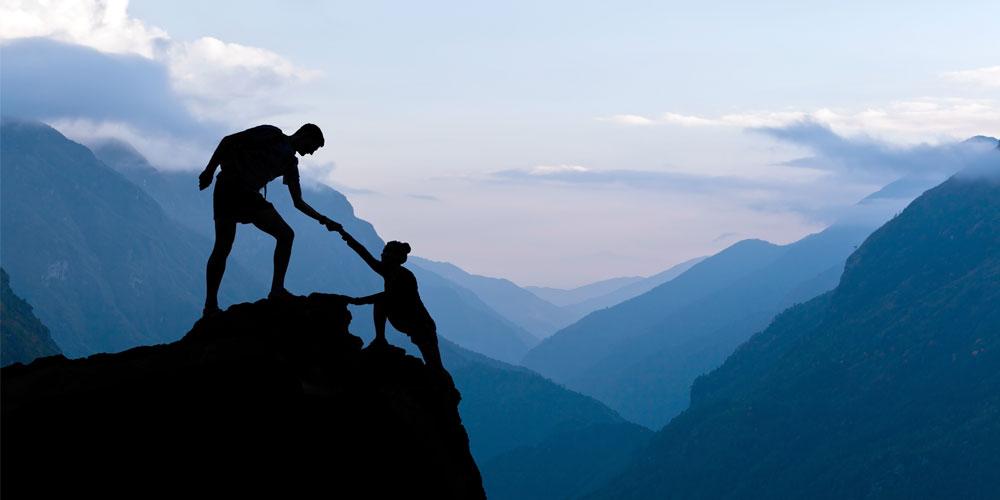 man helping woman climb cliff