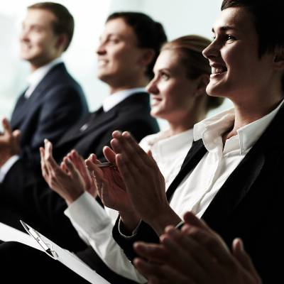 Tilt up of roup of business people applauding to a successful speaker